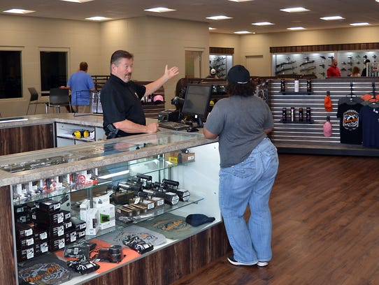 A Two Gun Tactical staff member assists a customer in their recently opened location at 667 Caseys Lane in Flowood.