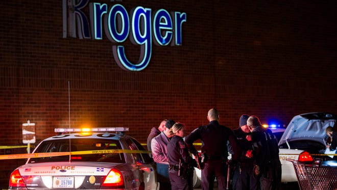 IMPD officers and investigators stand in the parking lot of a Southside Kroger where a man was stabbed Wednesday evening.