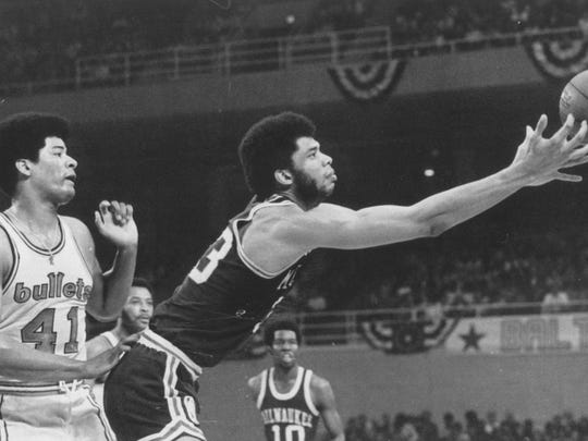 Milwaukee's Lew Alcindor, later known as Kareem Abdul-Jabbar, reaches for a loose ball while the Baltimore Bullets' Wes Unseld (left) looks on in the NBA Finals on April 30, 1971. The Bucks won the title, 4-0.