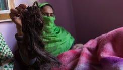 Shaqeela Sajad, holds up her chopped braid on Oct.