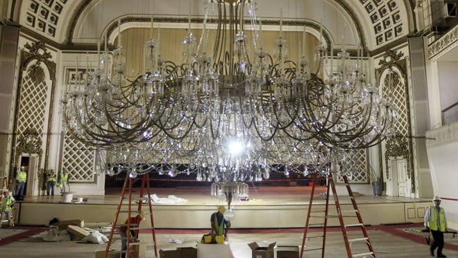 Workers have lowered and begun disassembling the main chandelier in Springer Auditorium.