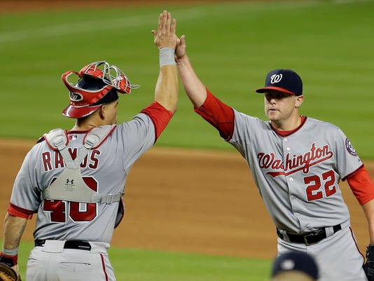 Washington Nationals relief pitcher Drew Storen (22) gets a high-five from catcher Wilson Ramos (40) at the end of a baseball game against the Miami Marlins in Miami, Friday, Sept. 19, 2014. The Nationals won 3-2. (AP Photo/Alan Diaz)