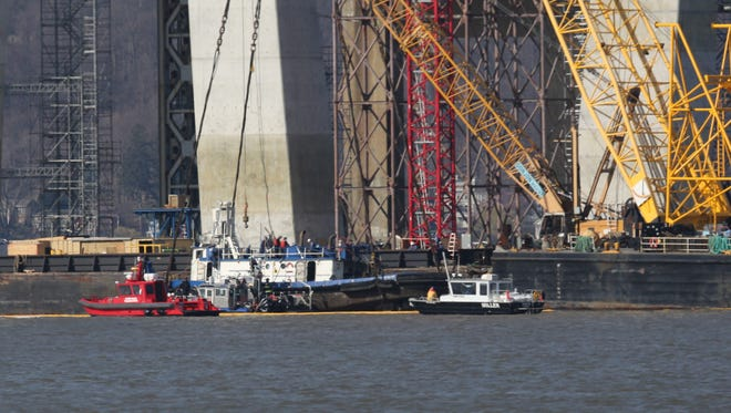 The tugboat Specialist is raised to the surface of the Hudson River under the Tappan Zee bridge, March 24, 2016, as emergency workers recover the body of Harry Hernandez and perform forensic examination on the vessel.