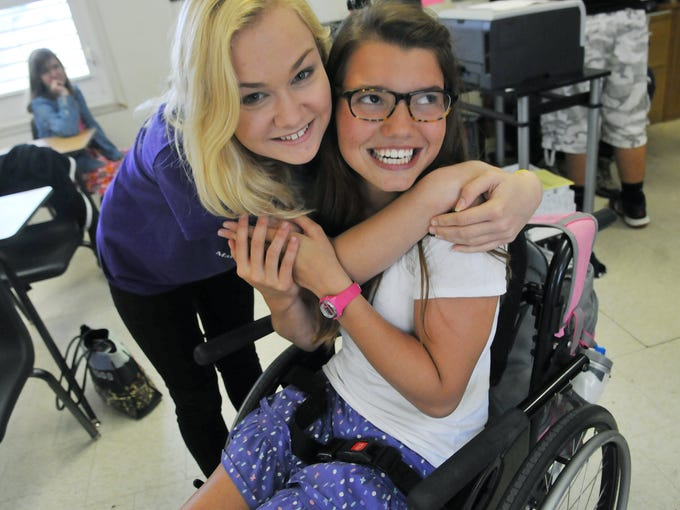 Seventeen-year-old Olivia DeBoer gets a hug from 15-year-old