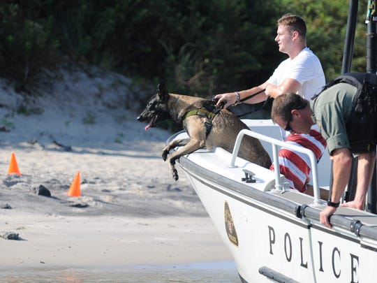 Brad Martz, Queen Anne's County Police k-9 handler, awaits the water training drill with his partner Spike on Monday, Aug. 16, 2016 near the Ocean City harbor.