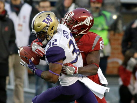 Washington defensive back Budda Baker  intercepting a pass intended for Washington State receiver John Thompson.