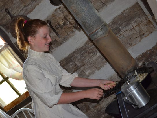 Lily Arnold stirs lard on the stove in the Annie Brown