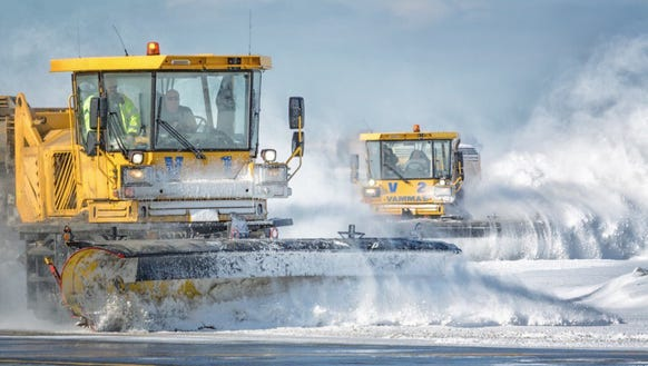 Plows clear snow from one of the airports run by the