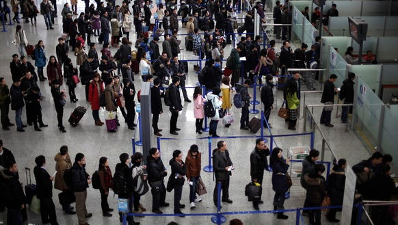 Passengers line up for a security check at Pudong International