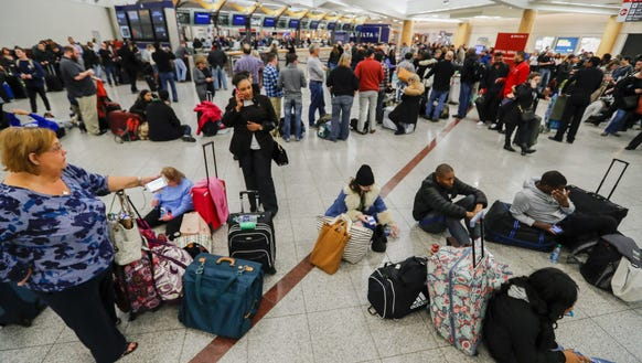 Stranded Delta Air Lines passengers wait to check in