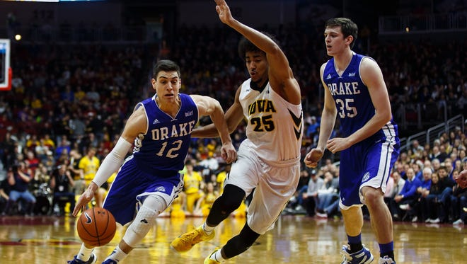 Drake's Reed Timmer drives to the basket against Iowa's Dom Uhl during the teams' Big Four Classic game at the Wells Fargo Arena on Saturday, December 19, 2015 in Des Moines.
