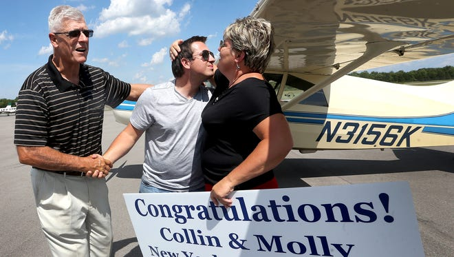Collin McDonald, center, gets a hand shake from his Dad David McDonald, left and a hug from his mom Lorrie McDonald, right, after he returned to Murfreesboro, on Thursday, June 16 2016, after Collin McDonald completed a transcontinental flight as part of a honors thesis project at MTSU.