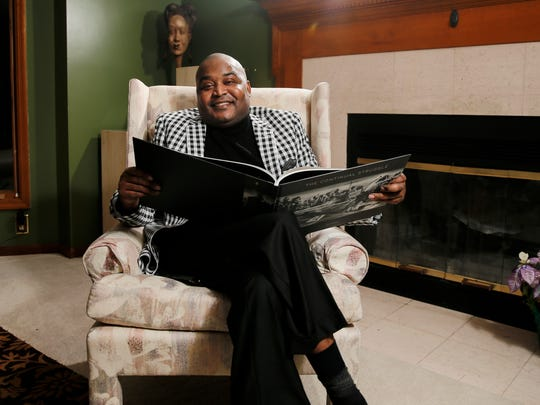 "Brian Washington, 36, pictured at his home with a copy of his book, ""The Continual Struggle,"" Tuesday, Jan. 10, 2017, produces art inspired by the Civil Rights movement. The purpose of his art is to educate and inspire to make progress on social issues that are ""unfortunately recurrent,"" he said."
