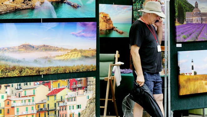 Paul James of Chelsea is a photographer being patient with the weather during the  Ann Arbor Art Fair.