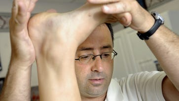 Dr. Larry Nassar works with a patient in this 2008 photo.