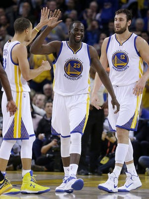 Golden State Warriors' Draymond Green, center, celebrates a score against the Indiana Pacers with Stephen Curry, left, and Andrew Bogut on Jan. 7, 2015.