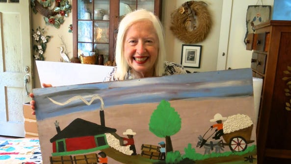 Maggie Martin holding a Clementine Hunter painting