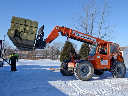 Nick Backhaus, left, and Rob Gille, right, of the Heritage Hill State Historical Park staff, and Mike Meland of Lamkin Trucking, Manawa, unload the first shipment of sixteen-foot logs, to be used to build the stockade fence at the Fort Howard Guard House and Commanding Officer's Office exhibit.
