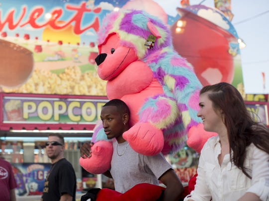 Willie Clark carries a large stuffed animal he won for his wife Nichole Clark and daughter Ahriyah Clark.