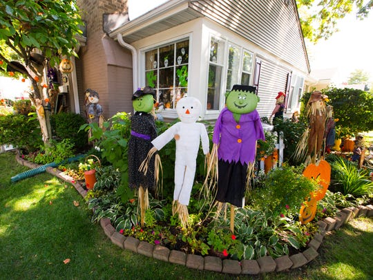 Friendly-looking scarecrows stand guard in a flower bed at the corner of the house.