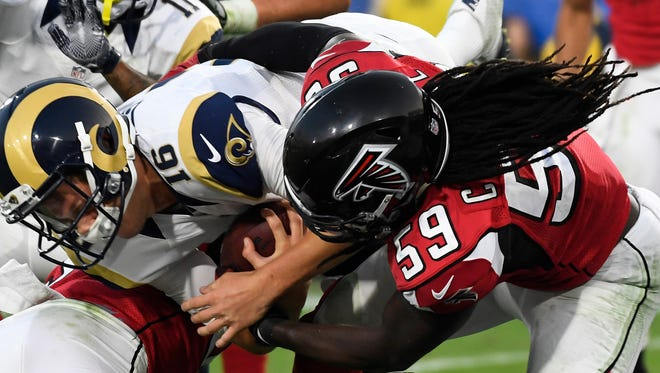 Los Angeles Rams quarterback Jared Goff (16) gets hit by Atlanta Falcons and former Cypres Lake High outside linebacker De'Vondre Campbell (59) as he scores a fourth quarter touchdown on a short run at the Los Angeles Memorial Coliseum. Mandatory Credit: Robert Hanashiro-USA TODAY Sports