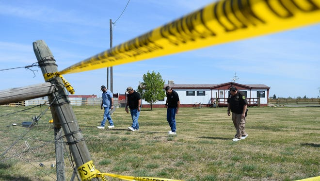 Law enforcement investigators walk the property at 5029 66th Ave. S.W. on Wednesday as they investigate the death of Adam Petzack, who was reported missing earlier this year. Brandon Lee Craft, a former resident at the at the address, is accused of killing Petzack and burying his body on the property.