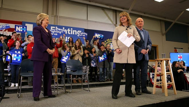 Hillary Clinton looks on as Gabbu Giffords and her husband, Mark Kelly, speak during a campaign event at Winnacunnet High School in Hampton, N.H., on Feb. 2, 2016.
