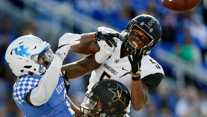 A pass in the end zone intended for Kentucky wide receiver Dorian Baker (2) is broken up by Vanderbilt cornerback Torren McGaster (5) and safety LaDarius Wiley (13) in the first half Saturday.
