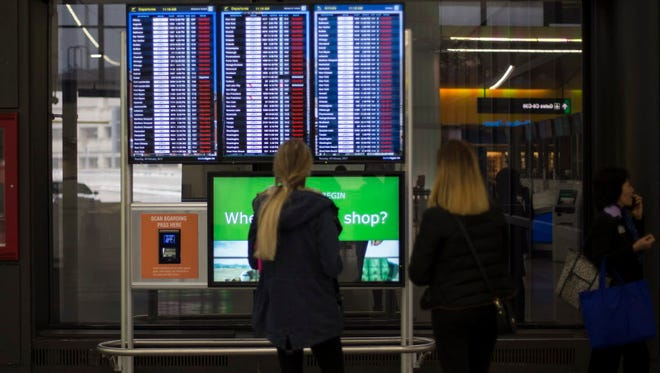 Travelers look over the flight information board that displays multiple cancellations at Logan International Airport in Boston, Mass., on Feb. 9, 2017.