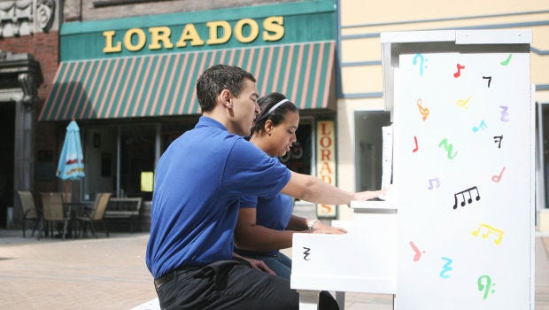 Elijah Warfield and Daniella Debrah play piano and sing Saturday, May 17, 2014, at one of four public pianos installed in downtown Mason, Iowa, provided through the efforts of 20 Mason City high school juniors in a project called Tunes for the Town.