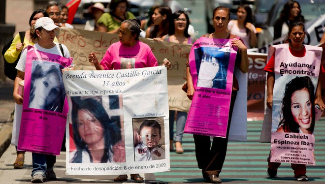 Mothers carry posters of their daughters who disappeared in Ciudad Juarez during a June 18, 2013, protest in Mexico City demanding police investigate the cases of missing women in the border area.