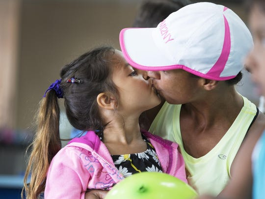 Davina McNaney kisses her daughter Nadja during a lunch break in Rochester on July 2, 2015.