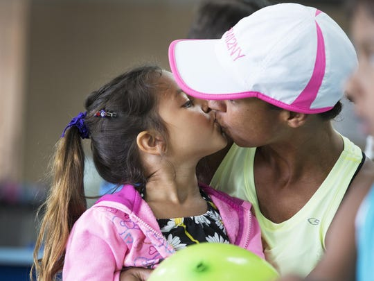 Davina McNaney kisses her daughter, Nadja, 7, during a lunch break in Rochester.