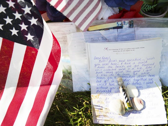 Amy Pierson leaves a letter, a vial of sand, and sea shells for Daryl at his grave in White Haven Memorial Park on Thursday, July 16, 2015. Amy collected sand and sea shells from the Outer Banks in North Carolina, where she and Daryl were married and often visited.