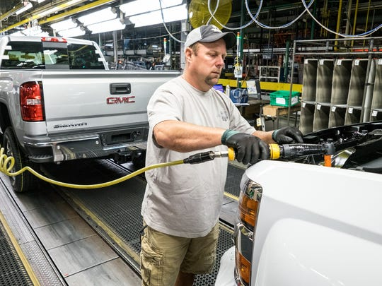 General Motors Flint Assembly employee Dan Hippensteel attaches the grille to the front of a GMC Sierra 2500 HD truck Tuesday, August 4, 2015 in Flint, Michigan.