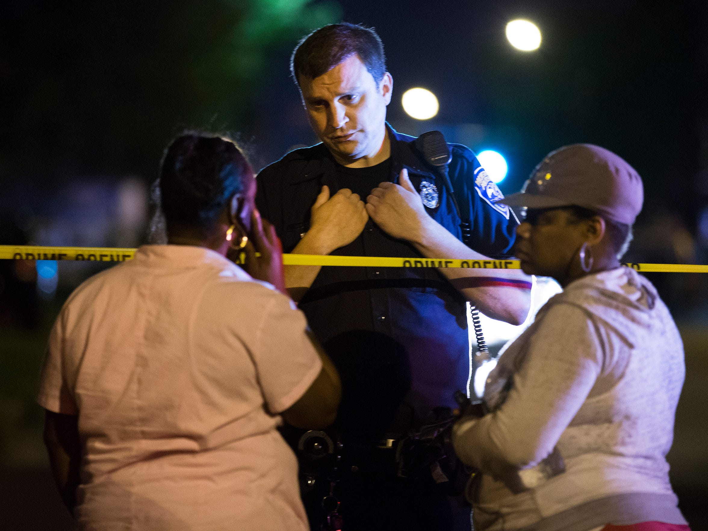 A Rochester Police Officer speaks to bystanders at the scene on Genesee Street near the Boys & Girls Club.