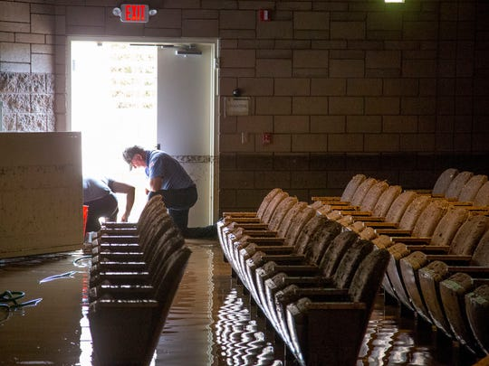 Church members and volunteers try and clean up flood