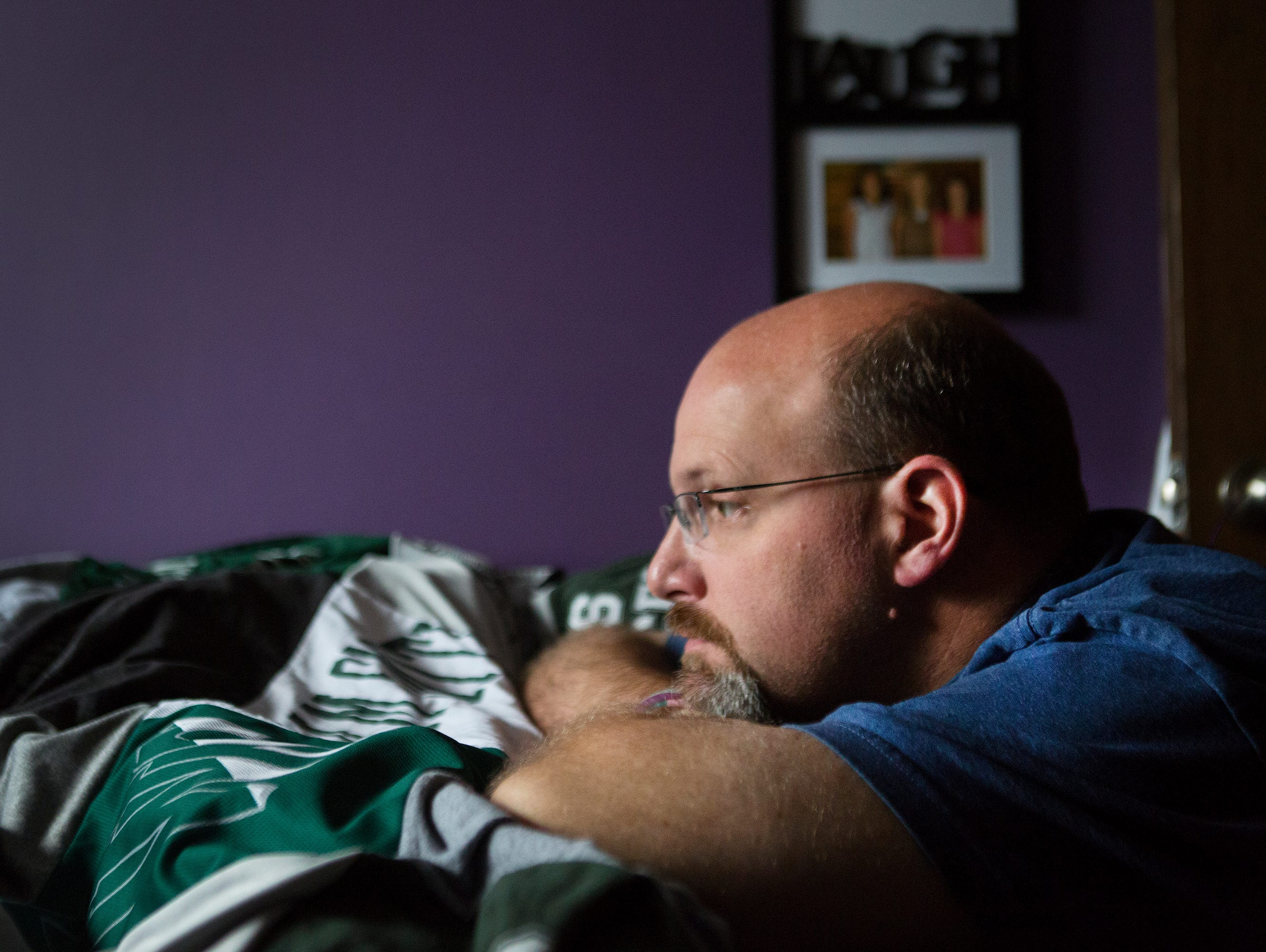 """Courtney Wagner's stepfather, Barry Clark, rests his head at the foot of Courtney's bed in their home in Farmington on Wednesday, October 21, 2015. He described the feeling of being in Courtney's bedroom saying, """"It's very calming. It's peaceful. It's tranquil. It's just easy to be there."""""""