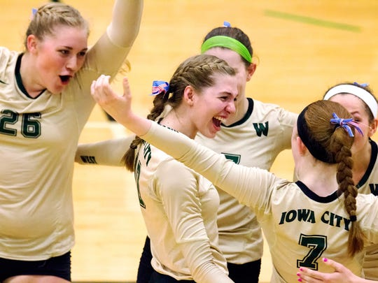 Iowa City West's Colby Greene (26), Ali Tauchen (10) and other teammates celebrate a point versus Iowa City High during their match at West High on Tuesday, September 8, 2015. (Justin Torner/Freelance for the Press-Citizen)