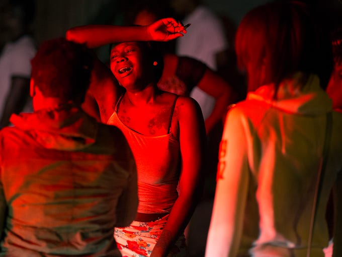 A young woman mourns at the scene of a shooting that