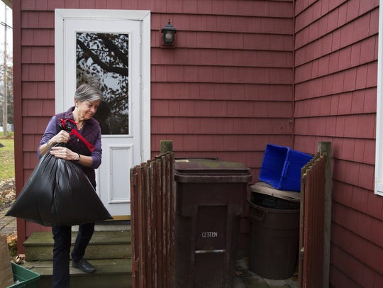Webster resident Deb Oakley takes her trash out for