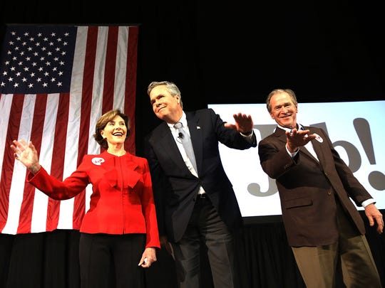 Jeb Bush stands with his brother, former president