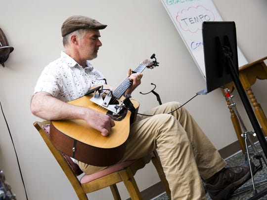Chris Colt signs and plays guitar during a rehearsal of the Aphasia Choir, made up of stroke survivors and others who have a communication disability.  The program is based at the Fanny Allen campus of the UVM Medical Center in Colchester.