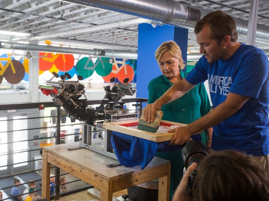 Raygun owner Mike Draper shows Hillary Clinton how to make a T-shirt during Clinton's stop at the East Village store on her presidential campaign in 2016.