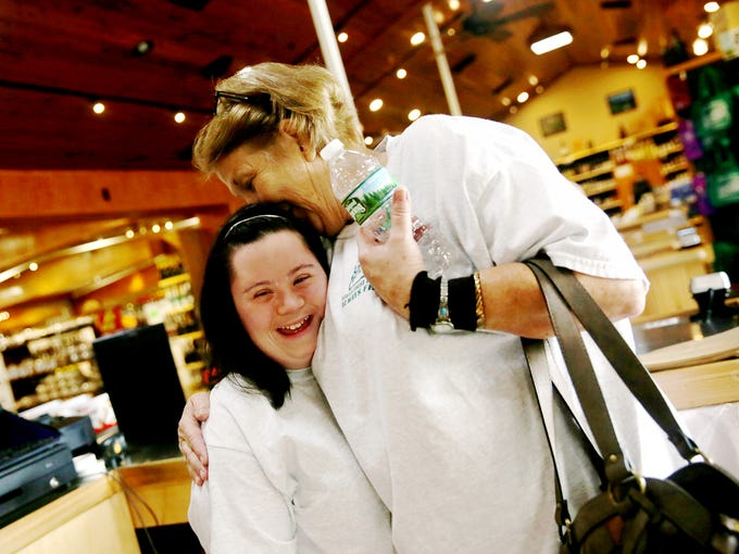 Cashier Sherry Phillips, right, hugs Caitlin Roggia,