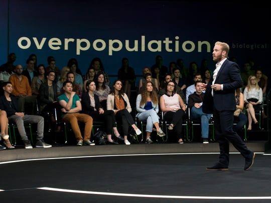 Zobrist (Ben Foster) presents his theory on overpopulation