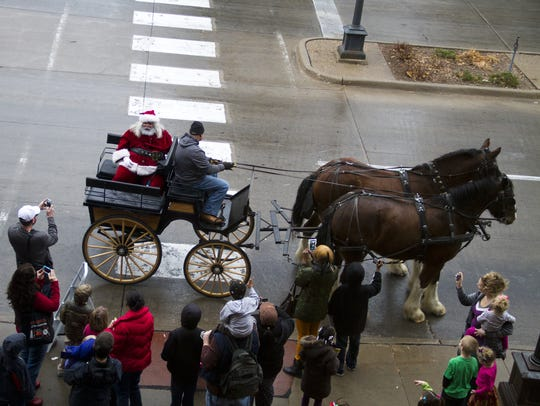 Santa arrives by horse-drawn carriage during Celebrate