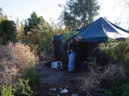 Cathedral City Police Officer Dwayne Hodge checks in on a homeless camp in a Cathedral City wash, Thursday, January 5, 2017.