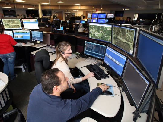 Tony Davino, center, a 911 shift leader at the Regional 911 Center in Newark, trains Jenna Lester, a dispatcher in training, Wednesday afternoon despite the loss of multiple computer services due to a virus. Law enforcement was hit particularly hard with 911 stations displaying blank screens seen in the background.