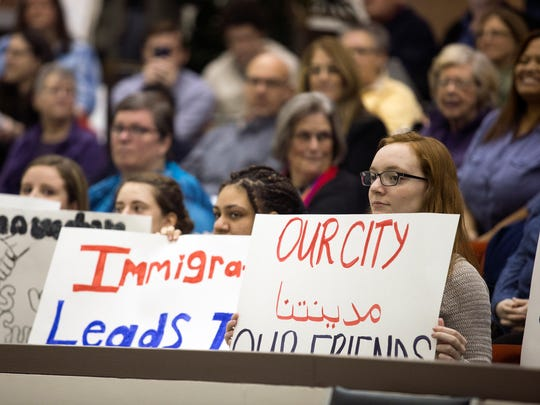 "Binghamton University students, including Mia Sager, 19, right, and Ashley Cambro, 20, center, hold signs in support of the proposed ""Welcoming Cities"" resolution during Wednesday's Binghamton City Council meeting."